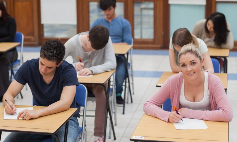 Students sitting at the exam room while concentrating with one looking up and smiling