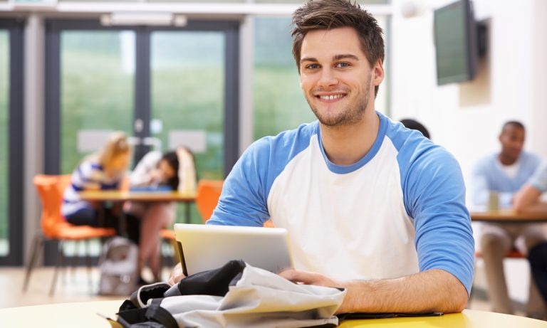 Male Student Studying In Classroom With Digital Tablet