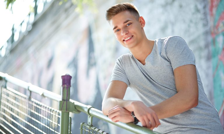 Portrait of young smiling man in the urban city